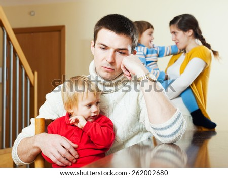 Young family with two children after quarrel at home - stock photo