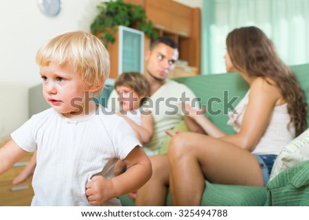 Young family with two kids having quarrel at home. Focus on girl - stock photo