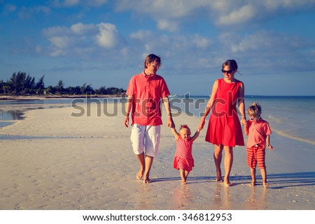 Young family with two kids walking at sand beach