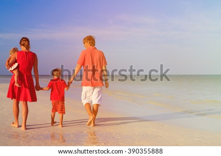 Young family with two kids walking on beach - stock photo