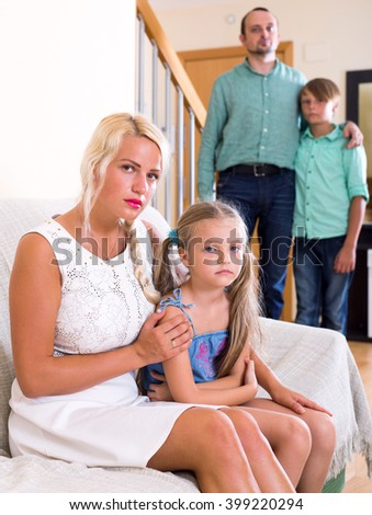 Young family with two little children having serious argue indoors - stock photo