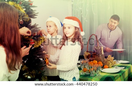 Young family with two little daughters decorating Christmas tree and serving table at home. Focus on girl - stock photo