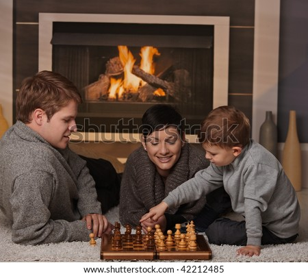 Young family with 4 years old kid playing chess at home in a cold winter day.