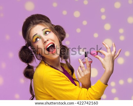Young fancy woman applying perfume on dotted background - stock photo