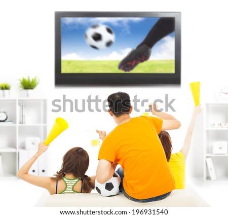 young fans yelling  and while watching soccer game - stock photo