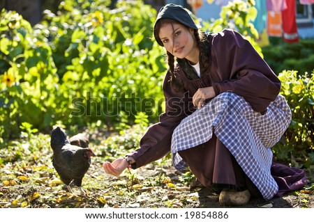 Young farm girl in traditional clothing feeding the chickens - stock photo