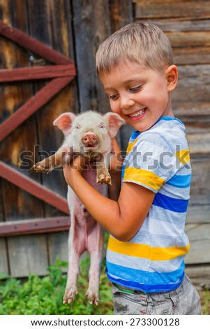 Young farmer - cute boy holding white piglet on a farm - stock photo