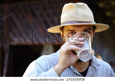 Young farmer drinking a glass of water in front of his wooden barn, selective focus - stock photo