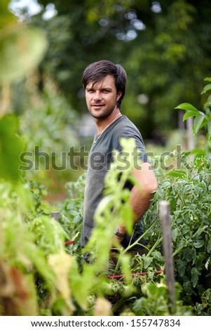 Young farmer in his orchard on a beautiful summer day