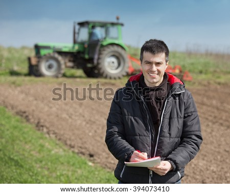 Young farmer supervising work and writing notes on farmland, tractor harrowing in background - stock photo