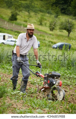Young farmer weeding in a corn field with a motorized tiller