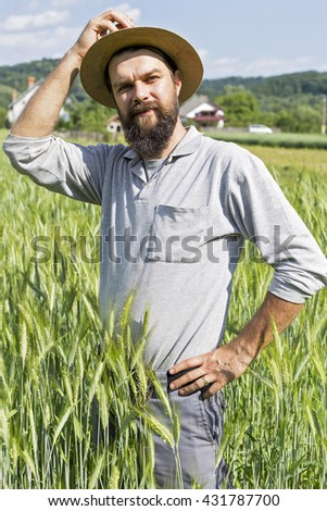 Young farmer with hat standing in the wheat field