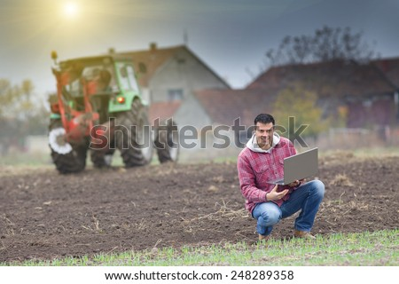 Young farmer with laptop on the field with seedlings in late autumn - stock photo
