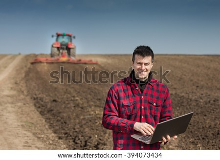 Young farmer with laptop supervising work on farmland, tractor harrowing in background - stock photo