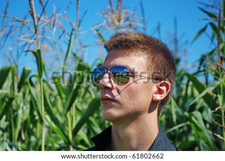 Young  farmer with sunglasses looking at the horizon.