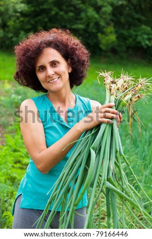 Young farmer woman with a sheaf of young onions in her garden - stock photo