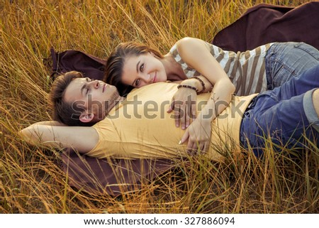 young fashion beautiful loving casual style couple lying down on floral field in autumnal park, warm sunny day, enjoying family, romantic date, happiness and love concept. resting and enjoying. - stock photo