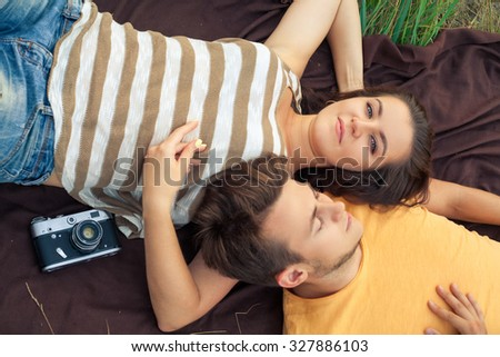young fashion beautiful loving casual style couple lying down on floral field in autumnal park, warm sunny day, enjoying family, romantic date, happiness and love concept. top view, with camera.
