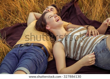 young fashion beautiful loving casual style couple lying down on floral field in autumnal park, warm sunny day, enjoying family, romantic date, happiness and love concept. happiness ans laugh. - stock photo