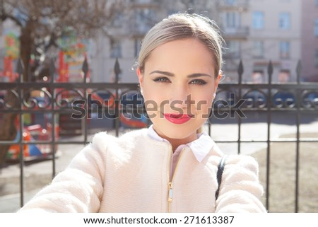 Young fashion beautiful woman in sunglasses on a city street. Selfie