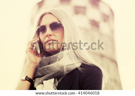 Young fashion blond business woman calling on cell phone. Female stylish model in sunglasses outdoor - stock photo