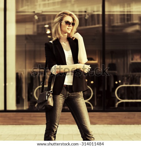 Young fashion blond business woman with handbag against a mall window - stock photo