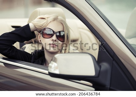 Young fashion blond woman driving convertible car  - stock photo