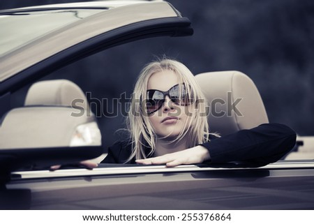 Young fashion blond woman driving convertible car