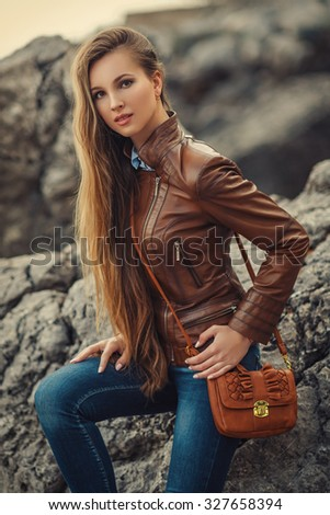 Young fashion blond woman in leather jacket on the city street - stock photo