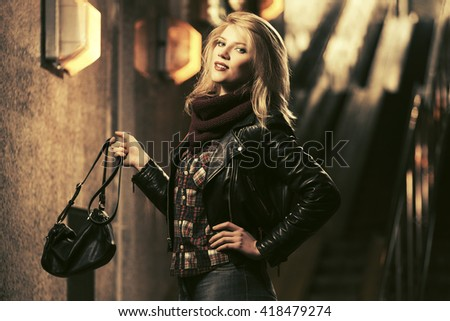 Young fashion blond woman with handbag. Female fashion model in black leather jacket - stock photo