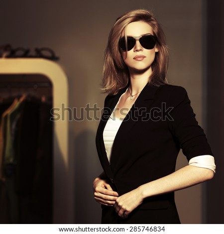 Young fashion blonde woman in sunglasses at the mall interior - stock photo