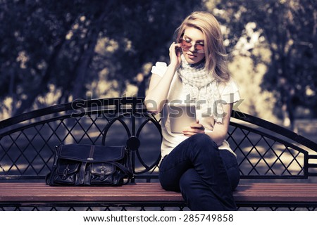 Young fashion blonde woman using tablet computer in a city park - stock photo