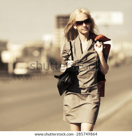 Young fashion blonde woman with handbag walking on a city street  - stock photo
