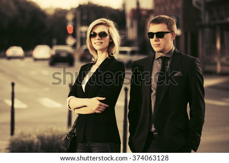 Young fashion business couple walking on city street - stock photo