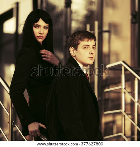 Young fashion business man and woman against office building - stock photo