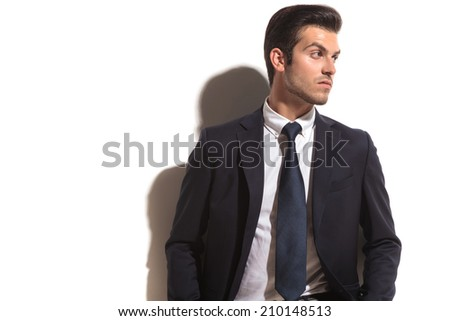 young fashion business man looking over his shoulder to his side, on white background