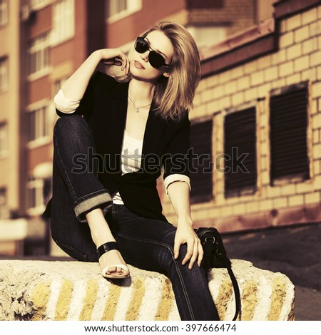 Young fashion business woman in sunglasses on city street - stock photo