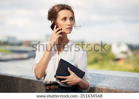 Young fashion business woman with handbag calling on mobile phone outdoor - stock photo