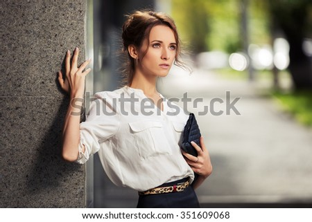 Young fashion business woman with handbag standing at office building - stock photo