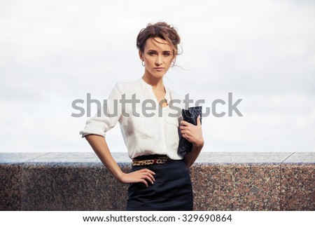Young fashion business woman with handbag walking on the city street - stock photo