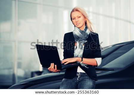 Young fashion business woman with laptop on the car parking  - stock photo