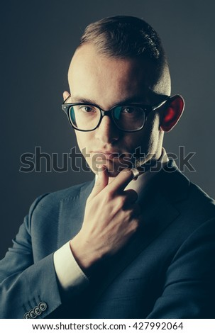 young fashion businessman with nerd glasses on thoughtful face and stylish hairdo in jacket with tie on studio background