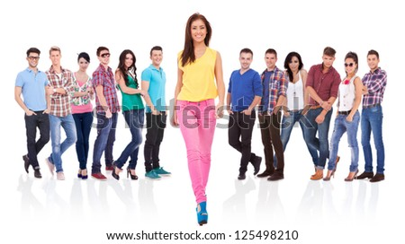 young fashion casual woman walking forward in front of a large team - stock photo