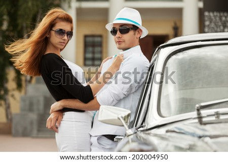Young fashion couple at the retro car - stock photo