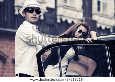 Young fashion couple by retro car - stock photo