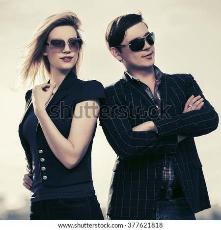 Young fashion couple in sunglasses walking on city street - stock photo