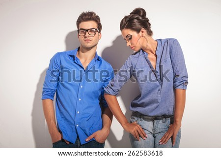 Young fashion couple leaning on a grey wall while looking away from the camera. - stock photo