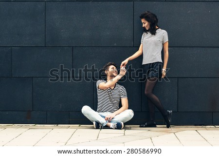 Young fashion couple near black wall. Pretty beautiful woman in stripes  clothes.  - stock photo
