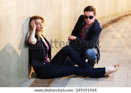 Young fashion couple sitting at the wall