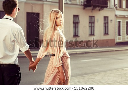 Young fashion couple walking down the street in summer in europe. Pretty beautiful woman looking in camera. Creamy sunlight - stock photo